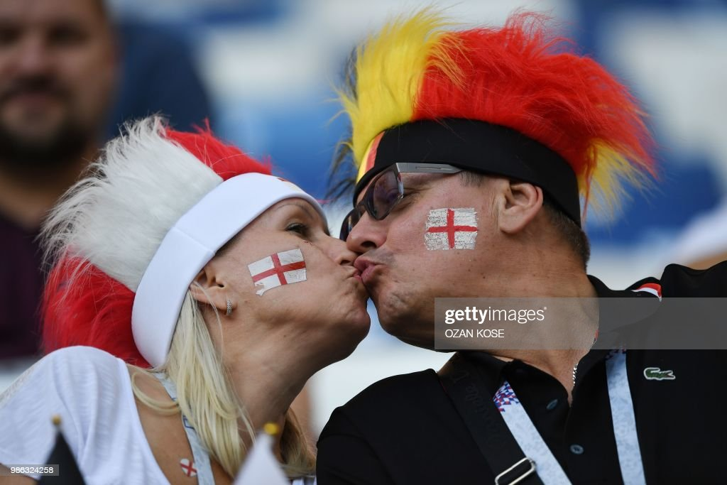 TOPSHOT - Fans of England and Belgium share a kiss before the Russia 2018 World Cup Group G football match between England and Belgium at the Kaliningrad Stadium in Kaliningrad on June 28, 2018. (Photo by OZAN KOSE / AFP) / RESTRICTED