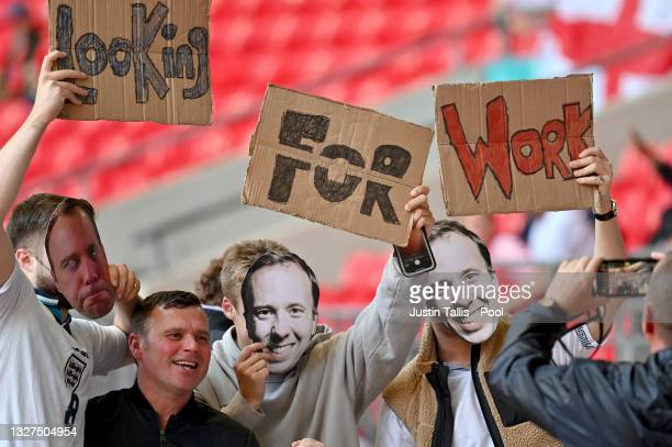 """Fans of England are seen with masks of Former Health Secretary, Matt Hancock with signs reading """"Looking For Work"""" prior to the UEFA Euro 2020..."""