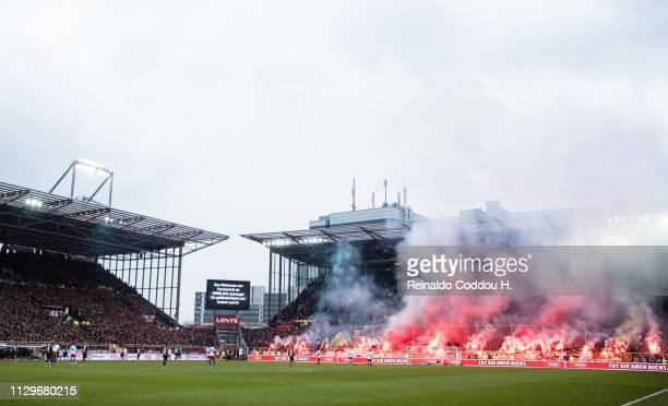 Fans of FC St Pauli burns flares during the Second Bundesliga match between FC St Pauli and Hamburger SV at Millerntor Stadium on March 10 2019 in...