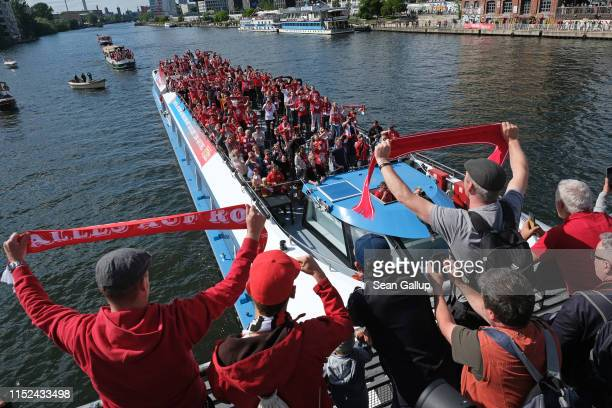 Fans of FC Union standing on Oberbaumbrücke bridge cheer as a boat carrying more fans passes below during celebrations for the club's promotion to...
