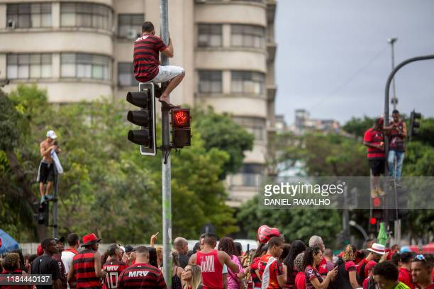 Fans of Flamengo football club take part in a celebration parade after the team's arrival following their Libertadores final match victory over...