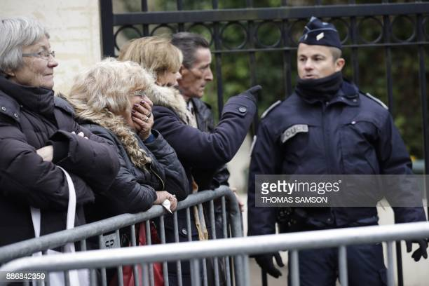 Fans of French singer and actor Johnny Hallyday react next to a policeman near the house of Johnny Hallyday in MarneslaCoquette on December 6 2017...