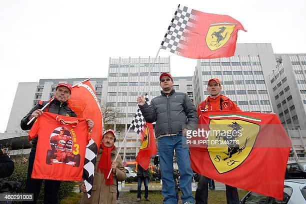 Fans of German Formula One world champion Michael Schumacher hold F1 Ferrari team flags and a Tshirt with a picture of the former pilot on January 3...