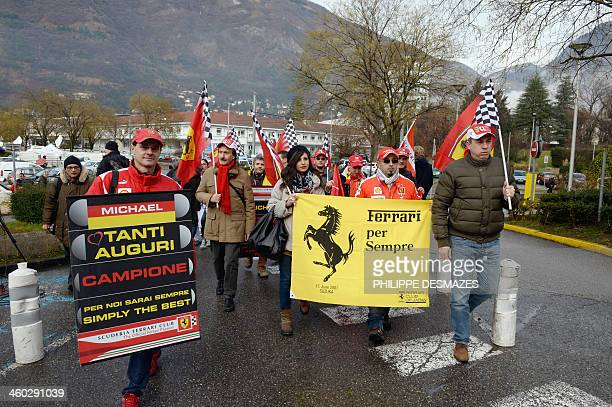 Fans of German Formula One world champion Michael Schumacher hold F1 Ferrari team flags and message of support on January 3 as they walk to the...