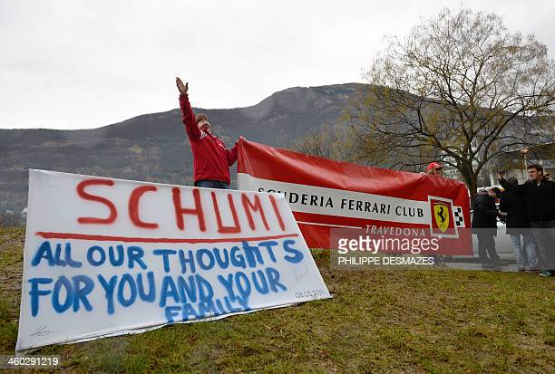 Fans of German Formula One world champion Michael Schumacher put a sign with messages of support and a banner of F1 Ferrari team on January 3 in...