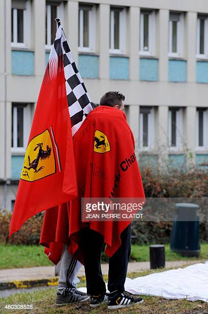 Fans of German Formula One world champion Michael Schumacher wear flags of the Ferrari Formula One team as they stand in front of the Grenoble...
