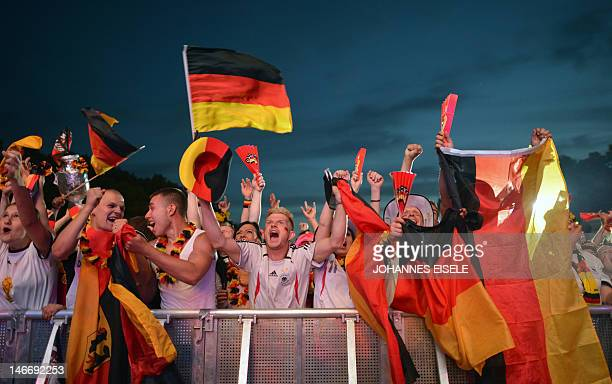 Fans of German national football team celebrate a goal scored by their team during a public viewing event in Berlin showing the EURO 2012...