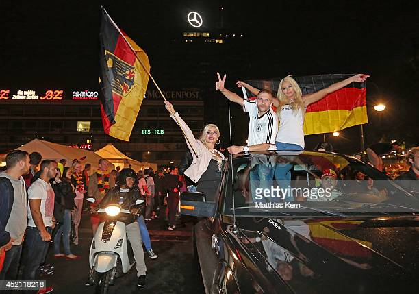 Fans of Germany celebrate at Kurfuerstendamm after their team winning the 2014 FIFA World Cup final match between Germany and Argentina on July 13...