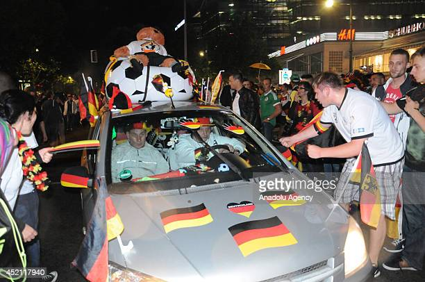 Fans of Germany celebrate their team's victory following the World Cup final soccer match between Germany and Argentina on July 14 2014 in Berlin...