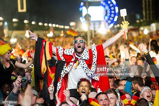 Fans of Germany cheer after Mario Goetze scored for Germany during the 2014 FIFA World Cup Final between Germany and Argentina at the Fanmeile public...
