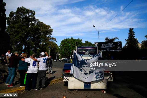 Fans of Gimnasia cheer for their team next to a flag with the image of Diego Maradona before a match between Gimnasia y Esgrima La Plata and...