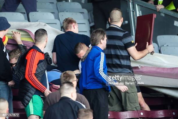 Fans of Hannover 96 rip up chair seats during the PreSeason Friendly between Burnley and Hannover 96 at Turf Moor on August 5 2017 in Burnley England