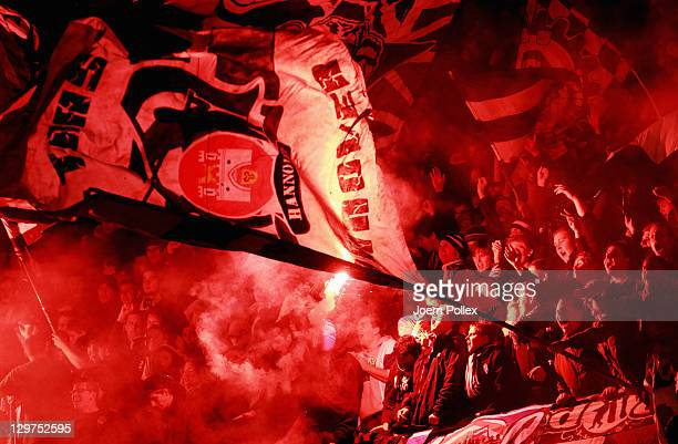 Fans of Hannover burn flares after Christian Pander of Hannover scored his team's first goal during the UEFA Europa League Group B match between...