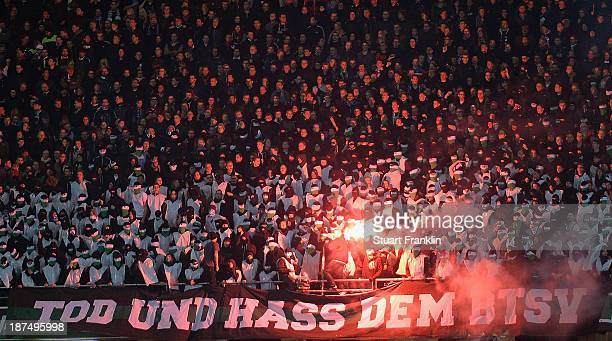 Fans of Hannover hold flares during the Bundesliga match between Hannover 96 and Eintracht Braunschweig at HDIArena on November 8 2013 in Hanover...
