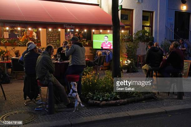 Fans of Hertha BSC football club sit outside at Fraenky sports bar to watch their team play against Berlin rival 1 FC Union during the coronavirus...