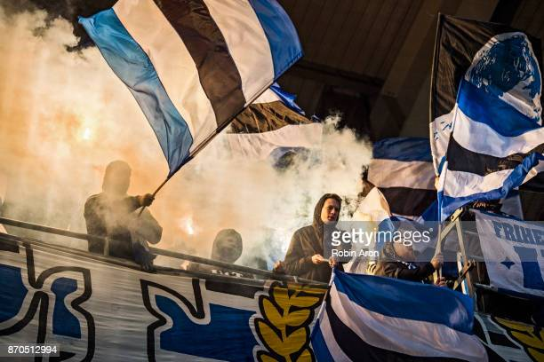 Fans of IFK Goteborg burning bengals and holding flags during the Allsvenskan match between IFK Goteborg and GIF Sundvall at Gamla Ullevi on November...