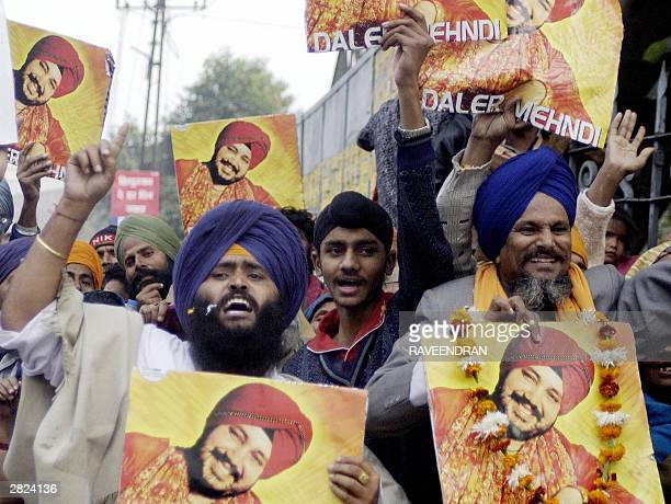 Fans of Indian singer Daler Mehandi shout slogans and wave pictures of Mehandi in front of the Tis Hazari Court in New Delhi 20 December 2003 as they...