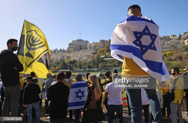 Fans of Israeli Beitar Jerusalem football club show their support during the team's training in Jerusalem on December 11 after a member of Abu...