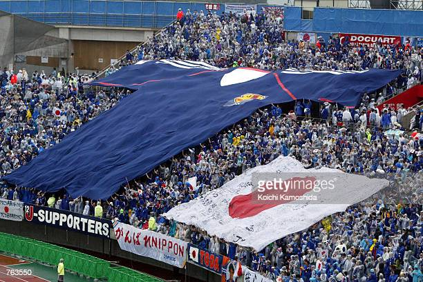 Fans of Japan's national soccer team unfurls a giant shirt and Japanese flag during halftime in a World Cup match against Turkey June 18 2002 in...