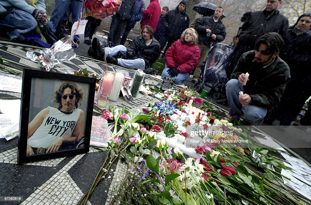Fans of John Lennon light candles and leave flowers as they  : Foto jornalística