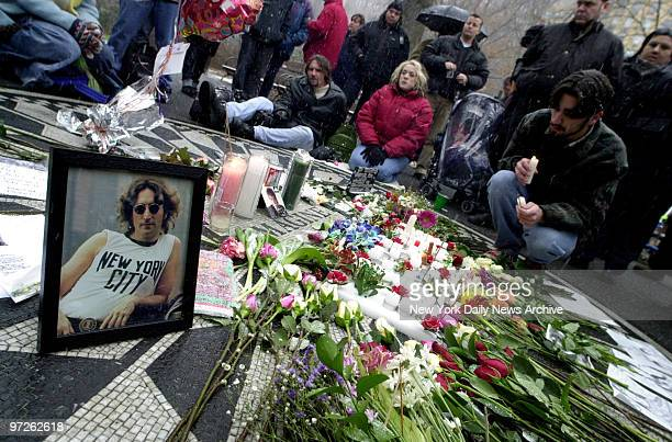 Fans of John Lennon light candles and leave flowers as they gather at Strawberry Fields in Central Park to commemorate the 20th anniversary of the...