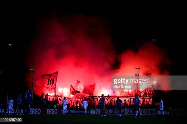 Fans of Karlsruher SC light flares during the DFB Cup round of sixteen match between 1. FC Saarbruecken and Karlsruher SC at...