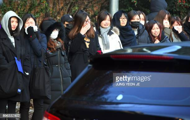 Fans of late SHINee singer Kim JongHyun cry as the hearse carrying the body of Kim JongHyun leaves from a hospital in Seoul on December 21 2017 Kim a...