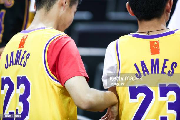 Fans of LeBron James of the Los Angeles Lakers use a Chinese National flag logo to cover the NBA logo while attending the match during a preseason...