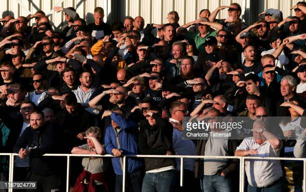 Fans of Leeds United shield their eyes from the sun during the Carabao Cup First Round match between Salford City and Leeds United at Moor Lane on...