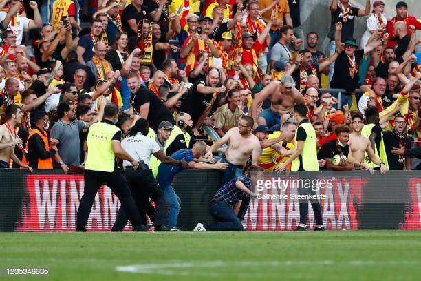Fans of Lens try to go on the pitch during the Ligue 1 Uber Eats match between Lens and Lille at Stade Bollaert-Delelis on September 18, 2021 in...