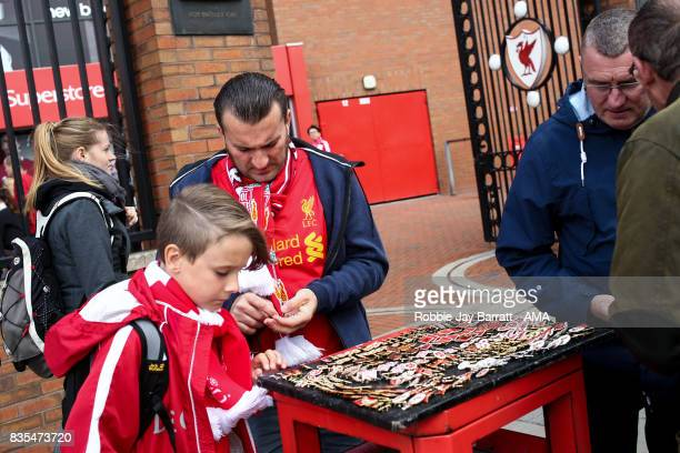 Fans of Liverpool buy pin badges prior to the Premier League match between Liverpool and Crystal Palace at Anfield on August 19 2017 in Liverpool...