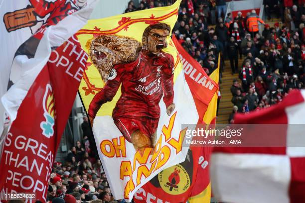 Fans of Liverpool celebrate Andy Robertson of Liverpool by waving flags and banners on The Kop during the Premier League match between Liverpool FC...