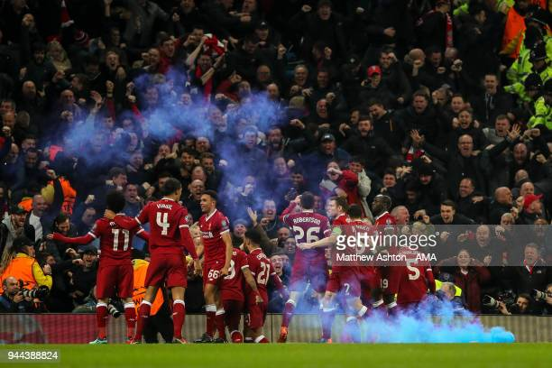 Fans of Liverpool celebrate as Mohamed Salah of Liverpool celebrates after scoring a goal to make it 11 and flares are thrown o the pitch during the...