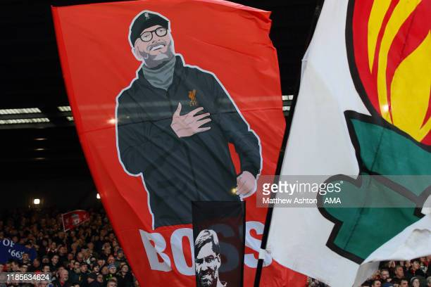 Fans of Liverpool celebrate Jurgen Klopp the head coach / manager of Liverpool by waving flags and banners on The Kop during the Premier League match...