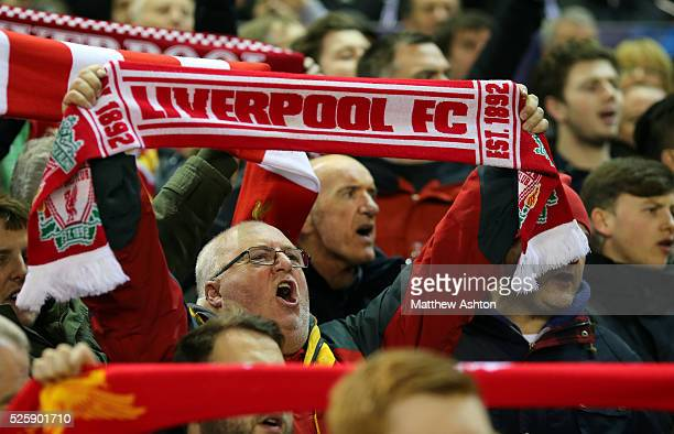 Fans of Liverpool sing YOU'LL NEVER WALK ALONE and hold up scarfs on The Kop at Anfield Stadium