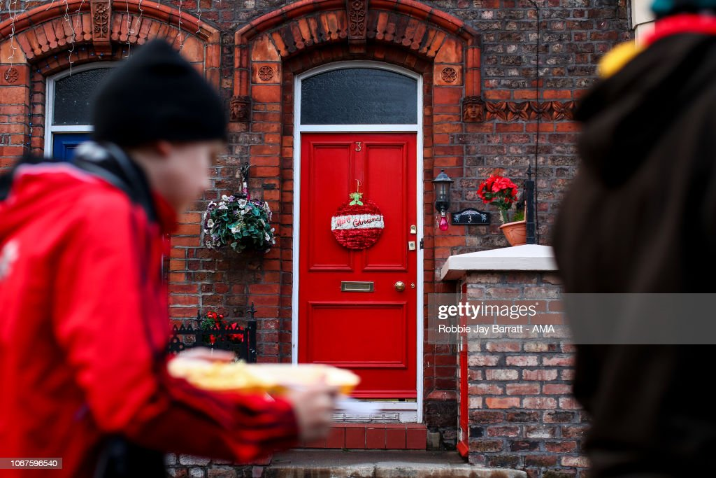 Fans Of Liverpool Walk Past A Red Door With A Merry