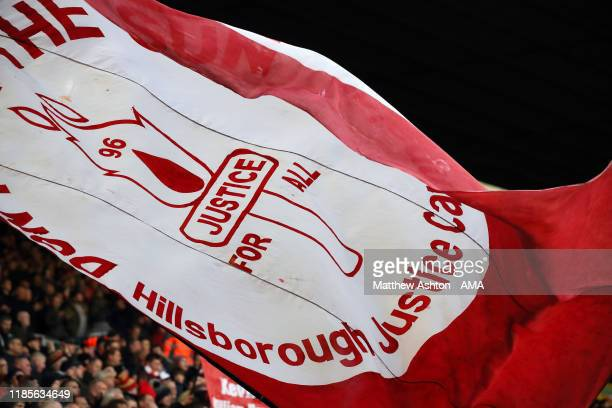 Fans of Liverpool wave Hillsborough justice flags and banners on The Kop during the Premier League match between Liverpool FC and Brighton Hove...