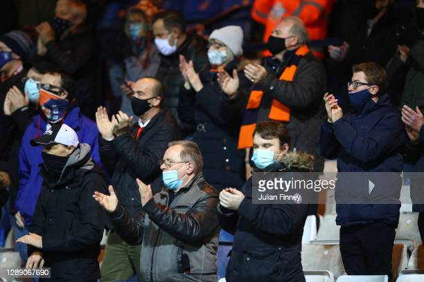 Fans of Luton Town applaud from their socially distanced seating whilst wearing a face mask ahead of the Sky Bet Championship match between Luton...