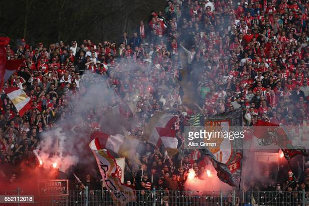Fans of Mainz burn flares during the Bundesliga match between SV Darmstadt 98 and 1 FSV Mainz 05 at JonathanHeimesStadion am Boellenfalltor on March...
