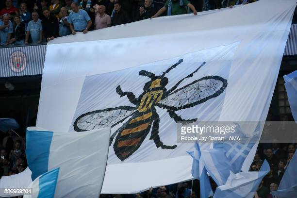 Fans of Manchester City hold up a flag of the symbolic Manchester Worker bee during the Premier League match between Manchester City and Everton at...