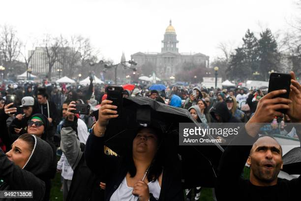 Fans of marijuana take pictures as 420 pm hits during 4/20 festivities at Denver's Civic Center Park on Friday April 20 2018
