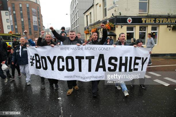 Fans of Newcastle make their way to the stadium with a banner ahead of the Premier League match between Newcastle United and Arsenal FC at St James...