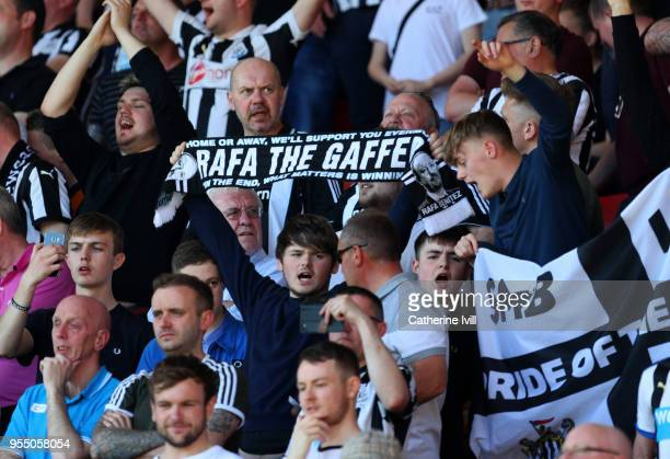 Fans of Newcastle United hold up a scarf bearing the name of Rafael Benitez Manager / head coach of Newcastle United during the Premier League match...