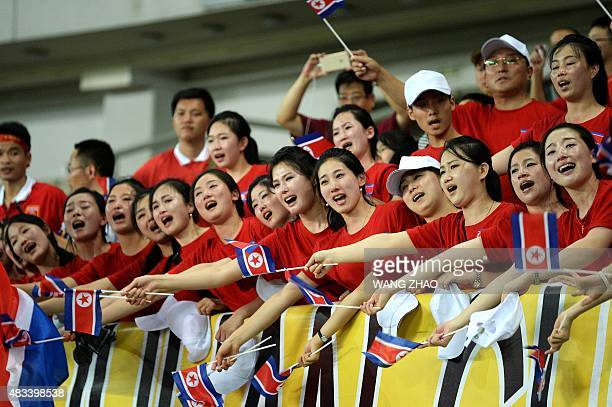 Fans of North Korea cheer during the Women's East Asian Cup football match between North and South Korea at the Wuhan Sports Center Stadium in Wuhan...