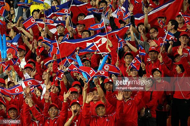 Fans of North Korea cheer on their team as they take on Japan during the women's gold medal football match at Tianhe Stadium during day ten of the...