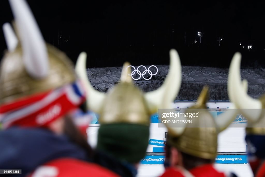TOPSHOT - Fans of Norway's Johannes Thingnes Boe celebrates look on during the victory ceremony in the men's 20km individual biathlon event during the Pyeongchang 2018 Winter Olympic Games on February 15, 2018, in Pyeongchang. / AFP PHOTO / Odd ANDERSEN