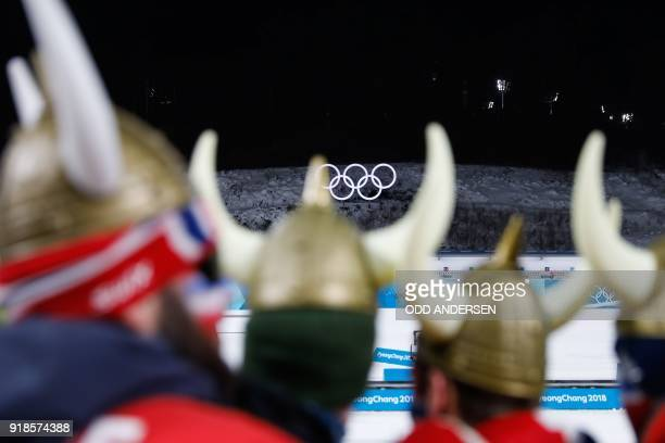 TOPSHOT Fans of Norway's Johannes Thingnes Boe celebrates look on during the victory ceremony in the men's 20km individual biathlon event during the...