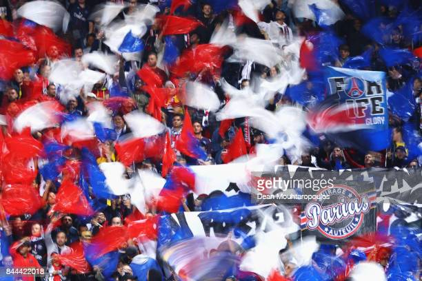 Fans of Paris Saint-Germain Football Club or PSG cheer and wave flags during the Ligue 1 match between Metz and Paris Saint Germain or PSG held at...