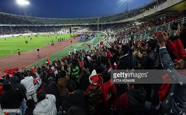 Fans of Persepolis FC cheer on their team during Iran's big derby match between Esteghlal and Persepolis at the Azadi stadium in Tehran on November...