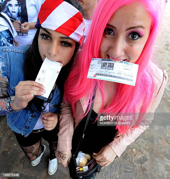 Fans of pop diva Lady Gaga currently on tour in South America show their tickets as they queue waiting to get inside the venue for the show the...